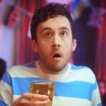 Man holding pint looking shocked